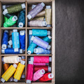 colored thread in a wooden in box on a black background - PhotoDune Item for Sale