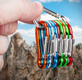 colorful carabiner climbing in hand on a background of mountains - PhotoDune Item for Sale