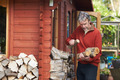 Mature Man Collecting Logs For Fire From Woodpile In Garden - PhotoDune Item for Sale