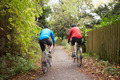 Two Mature Male Cyclists Riding Bikes Along Path - PhotoDune Item for Sale