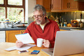 Mature Man Looking At Home Finances In Kitchen - PhotoDune Item for Sale