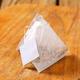 Pyramid-shaped tea bag on wood - PhotoDune Item for Sale