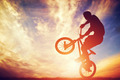 Man riding a bmx bike performing a trick against sunset sky - PhotoDune Item for Sale