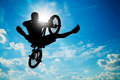 Man jumping on bmx bike performing a trick against sunny sky - PhotoDune Item for Sale
