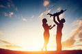 Happy family together, parents with their little child at sunset. - PhotoDune Item for Sale