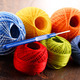 Colorful yarn for crocheting and hook on wooden table - PhotoDune Item for Sale