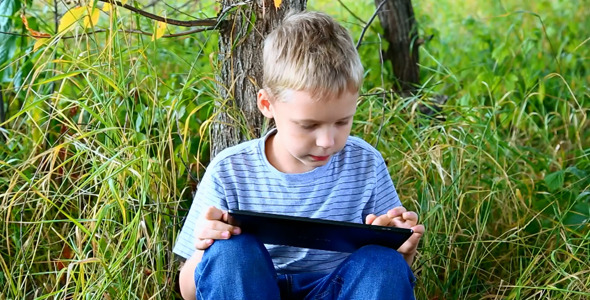 Kid Using Tablet Computer Touchscreen in Park