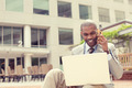 Businessman working with laptop outdoors talking on mobile phone - PhotoDune Item for Sale
