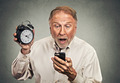 surprised business man with alarm clock looking at smart phone - PhotoDune Item for Sale