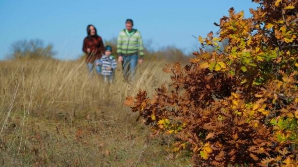 Family Walking In Autumn Meadow