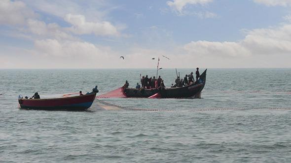 Fishermen In Boats Pulling Fishing Nets