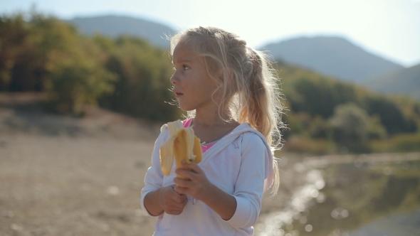 Amazing Little Girl Eating a Banana Near The Lake
