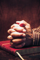 Praying with hands together in a Bible