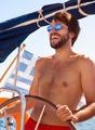 Happy guy behind wheel of sailboat - PhotoDune Item for Sale