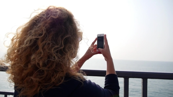 Woman Taking Pictures Of Sea With Smartphone