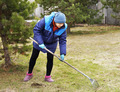 Woman gardener cleans a garden with the rake in spring - PhotoDune Item for Sale