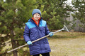 Woman gardener with a rake in the garden - PhotoDune Item for Sale