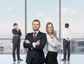 Happy young professionals are standing in a contemporary glass office in New York.