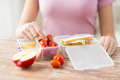 close up of woman with food in plastic container - PhotoDune Item for Sale