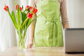 close up of woman with tulips in vase and laptop - PhotoDune Item for Sale