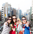 happy teenage girls showing thumbs up at city - PhotoDune Item for Sale