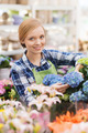 happy woman taking care of flowers in greenhouse - PhotoDune Item for Sale