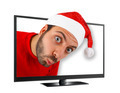 Young man with hat of Santa Claus comes out from the TV. - PhotoDune Item for Sale