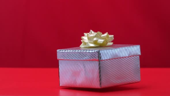 Gift Falling And Bouncing On Red Background