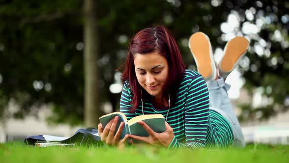 Pretty Student Lying On Grass Reading A Book Listening To Music