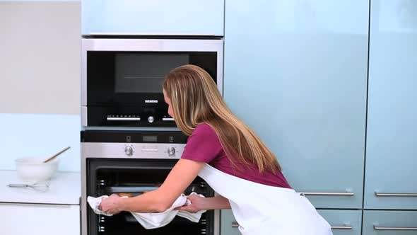 Blonde Woman Taking Cookies In Oven In Kitchen
