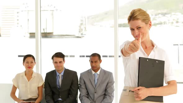 Businesswoman Giving Thumbs To Camera In Front Of Job Applicants