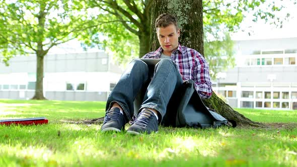 Young Student Sitting On The Grass Using Tablet Pc
