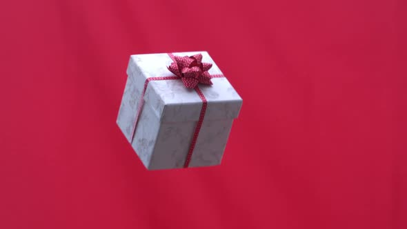 Christmas Present Tossed Into The Air On Red Background
