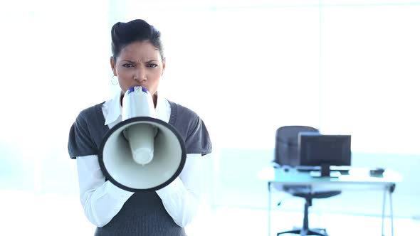 Serious Businesswoman Screaming In A Megaphone