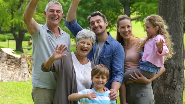 Multi Generation Family Smiling And Waving At Camera In A Park