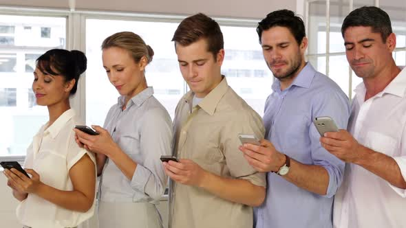 Content Businesspeople Text Messaging While Standing In A Row