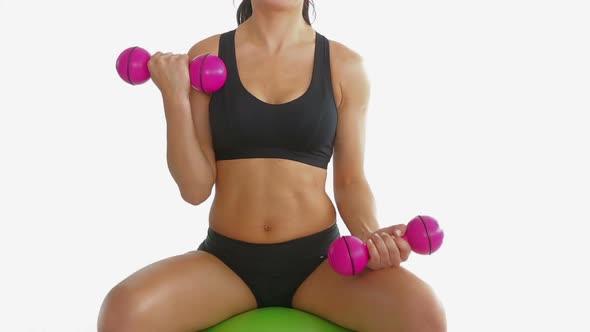 Toned Brunette Sitting On Exercise Ball Training With Dumbbells
