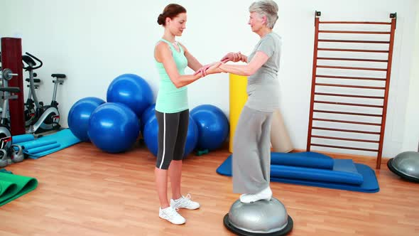 Trainer Helping Elderly Client To Use Bosu Ball