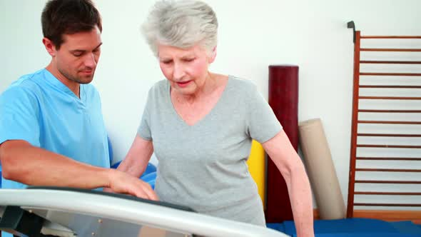 Physical Therapist Showing Patient How To Use Exercise Machine