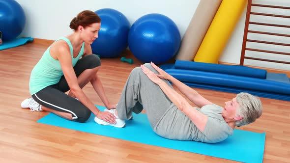 Trainer Helping Her Elderly Client Do Sit Ups