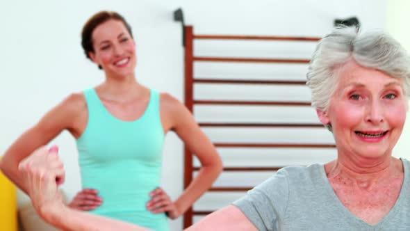 Trainer Watching Proud Elderly Client Flexing Her Bicep