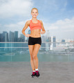 smiling sporty woman pointing at her six pack - PhotoDune Item for Sale