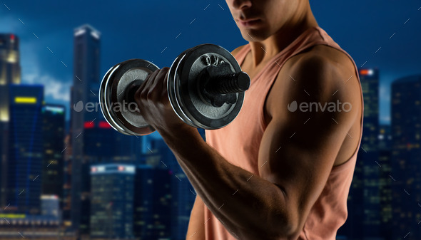 close up of young man with dumbbell flexing biceps