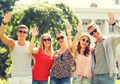 group of smiling friends waving hands outdoors - PhotoDune Item for Sale