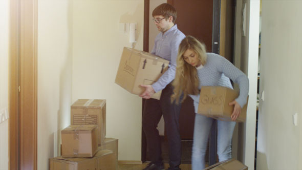 Couple Carrying Cardboard Box to Their New Flat