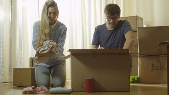 Couple is Unpacking Cardboard Boxes after Moving