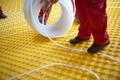workers installing underfloor heating system - PhotoDune Item for Sale