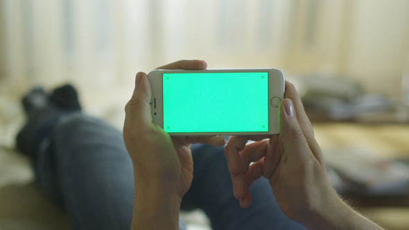Man is Laying on Couch at Home and Using Phone