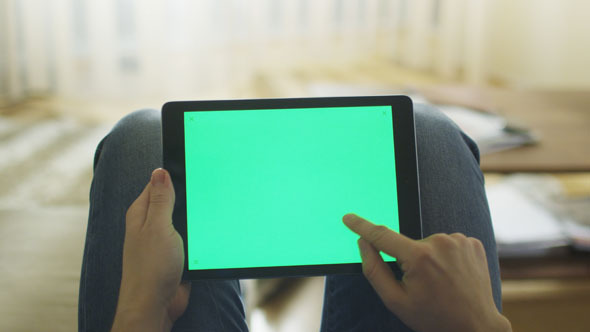 Man is Laying on Couch at Home and Using Tablet