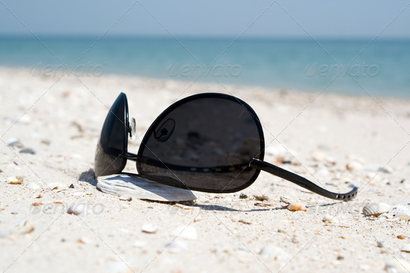 The black sunglasses lying on a beach - Stock Photo - Images